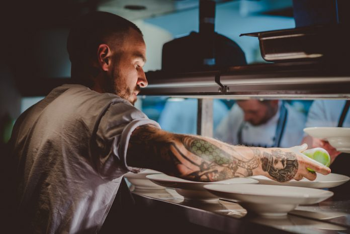Chef Gary Usher prepares the fish course at the pass at Restaurant 1539